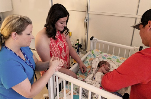 Physical therapist Carrie (left) consults with baby Liam's family in the NICU. Carrie is 1 of only 650 neonatal professionals in the country to have earned a certification in neonatal massage.
