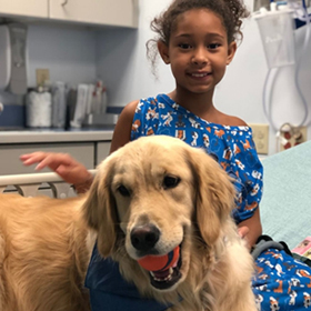 Little girl in a patient gown sitting with a Golden Retriever dog