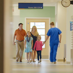 Little girl greeting a doctor as she and her family passes him in the hospital hallway